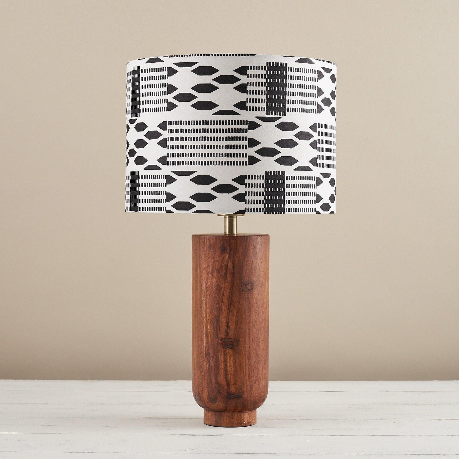 A lampshade with two different black and white graphic prints in squares all around it