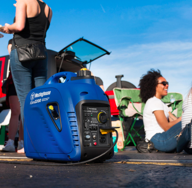 A blue gas-powered inverter generator on a curb next to people having a picnic