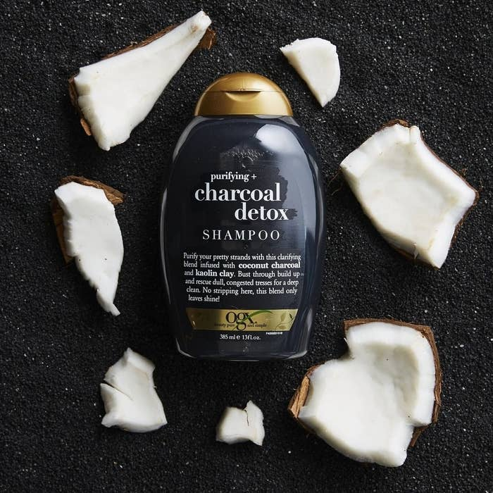 A flatlay of the shampoo bottle next to shattered shards of coconut
