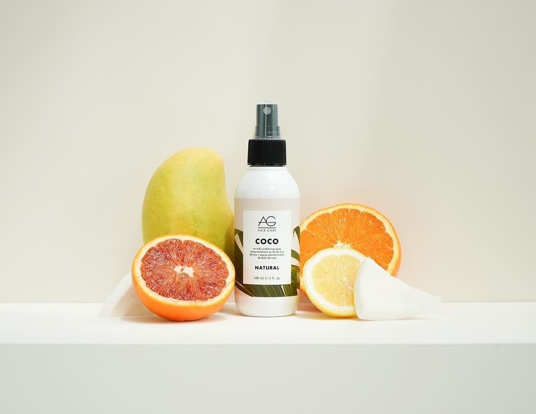 The bottle of hair mist next to some tropical fruits