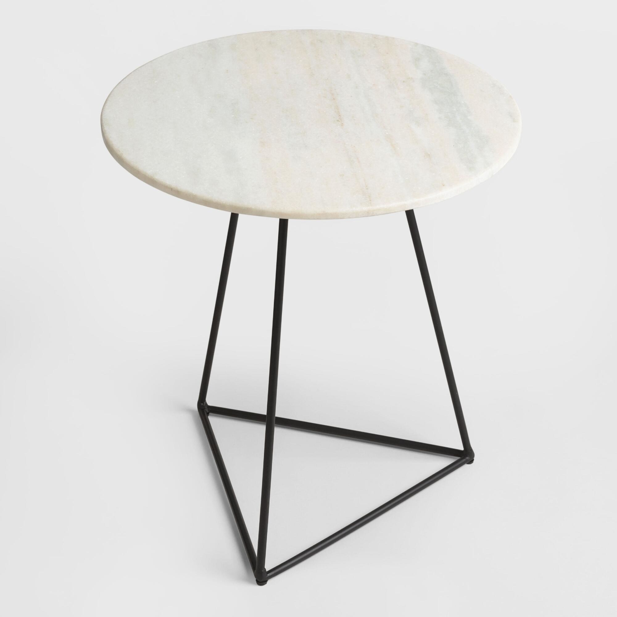 A round marble table with black metal triangle legs