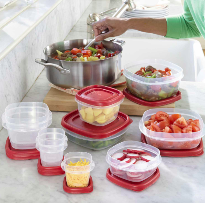 Hand holds spoon over pot next to red and clear food storage containers with fruit