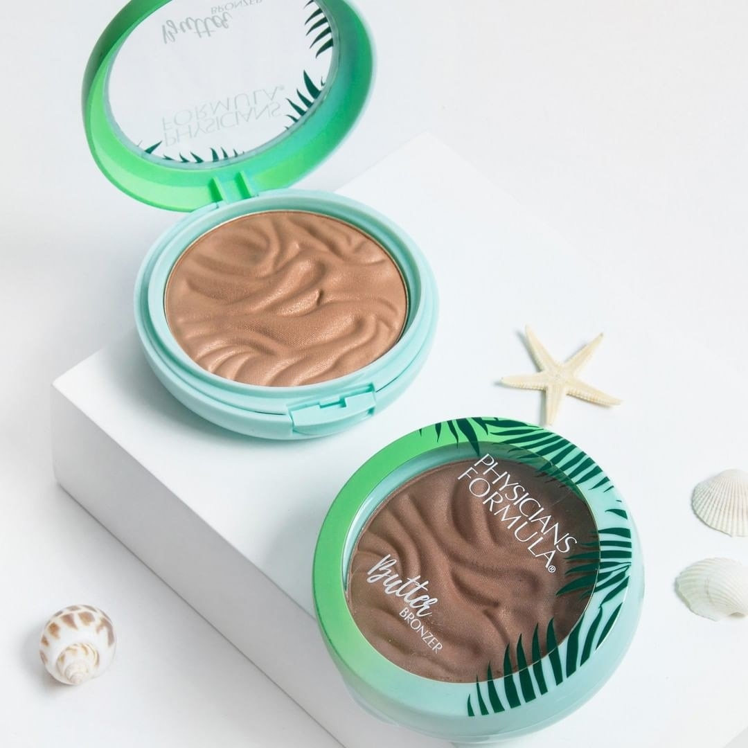 Two bronzers artfully arranged on a pale background with seashells