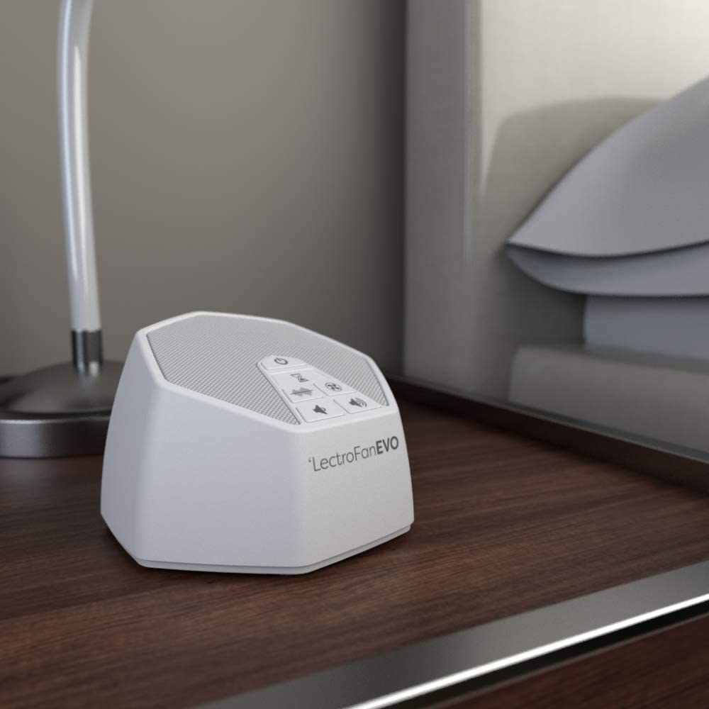 The small hexagonal white noise machine on a bedside table; it has a power button, two volume buttons, and three buttons for choosing the sound