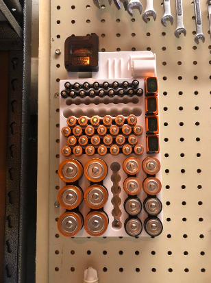 A review image of several batteries organized and hanging up by other tools