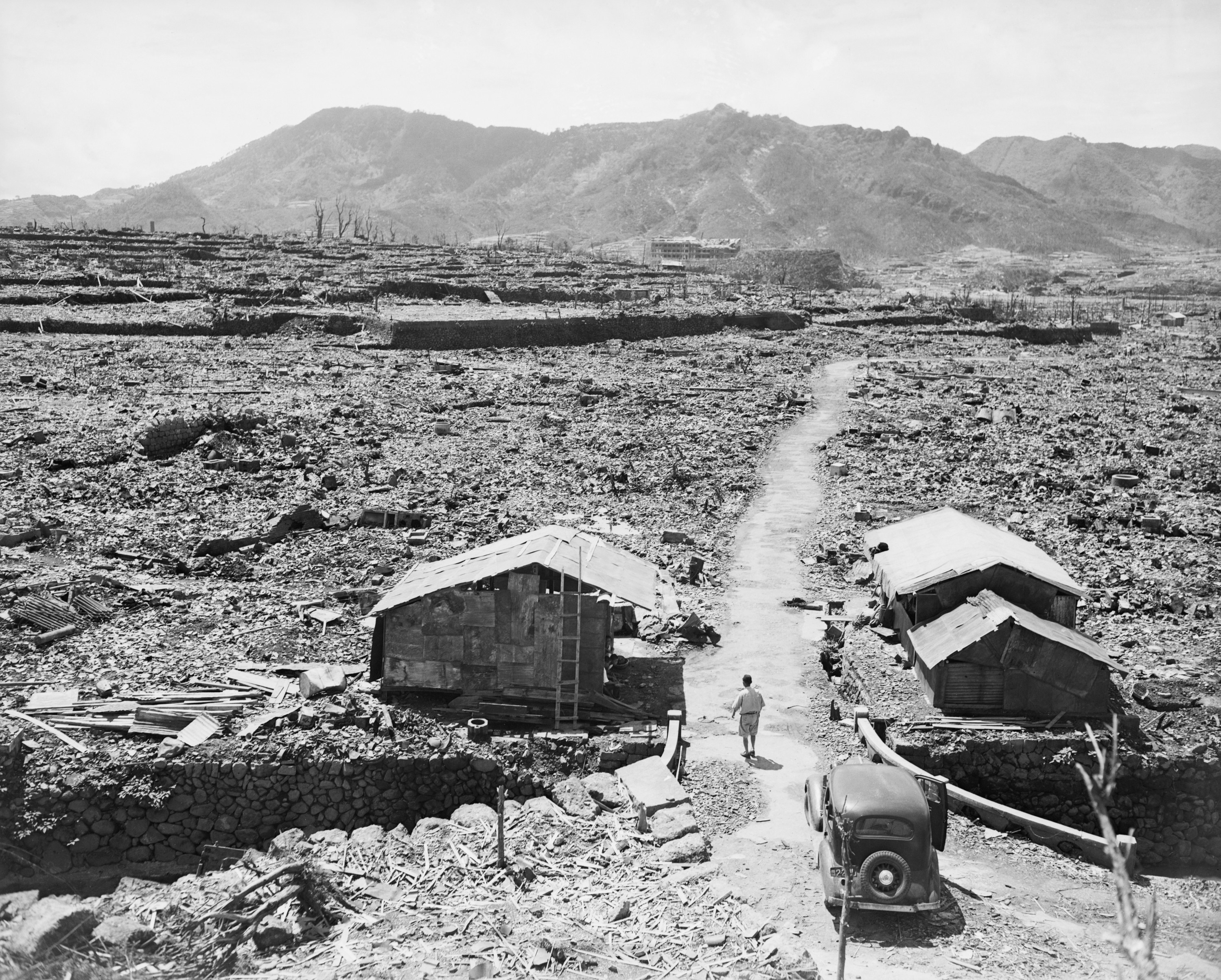 A man walks away from a car and toward a lone building standing amid rubble in a destroyed valley