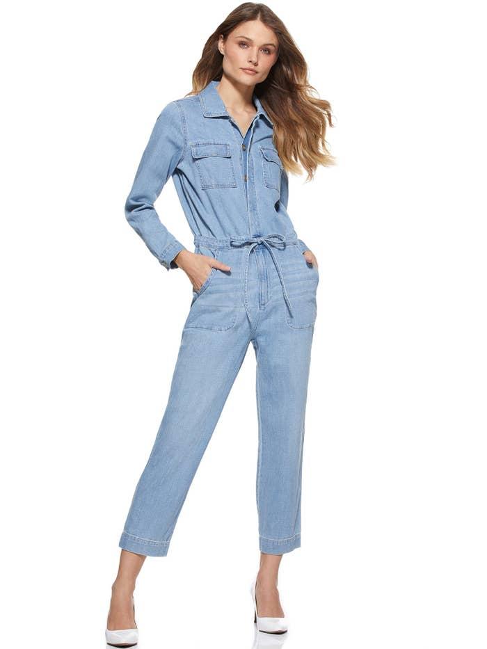 a model in a light blue denim jumpsuit