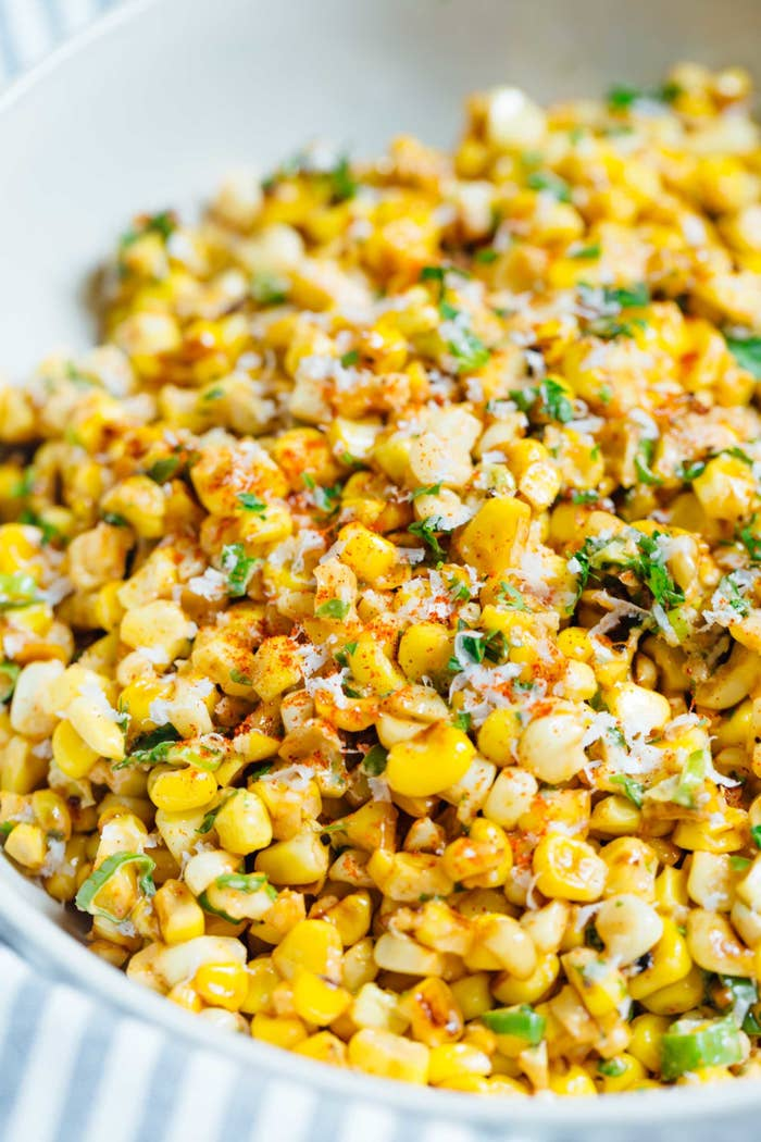 A corn salad with Cotija cheese, green onions, and cayenne pepper in a creamy dressing.