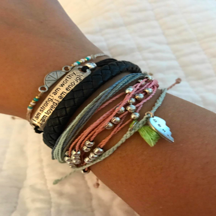 A reviewer wearing several small bracelets. The black braided cord bracelet blends in easily with the other accessories.