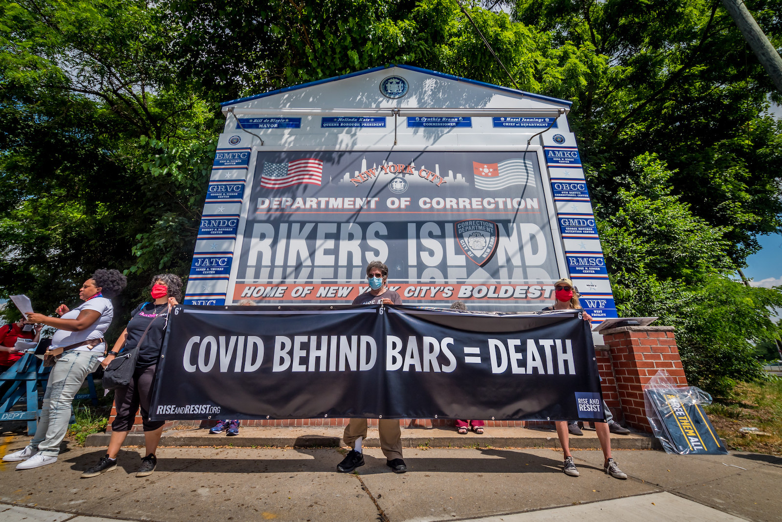 "People in masks hold up a banner reading ""COVID BEHIND BARS = DEATH"" in front of the sign for Rikers Island"