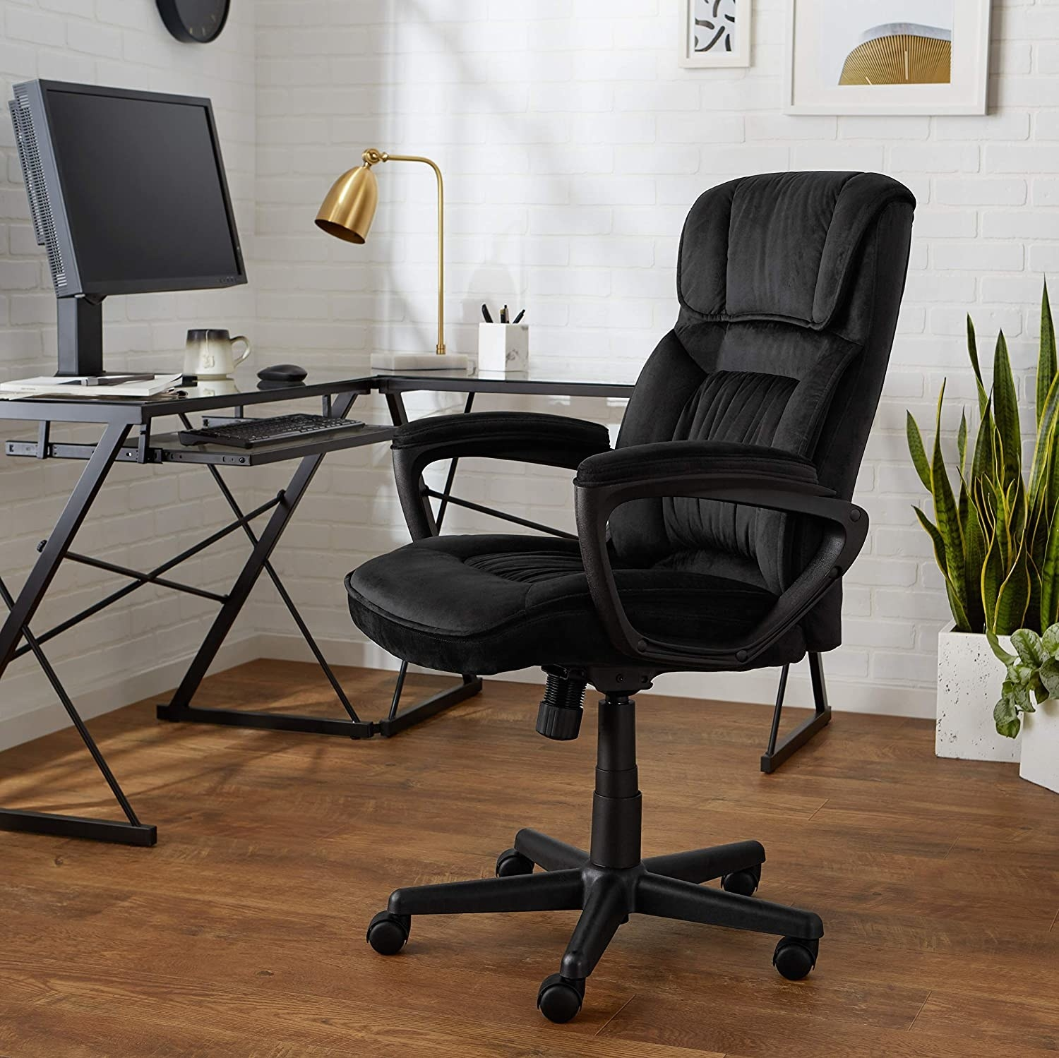 A large office chair with armrests sitting next to a desk