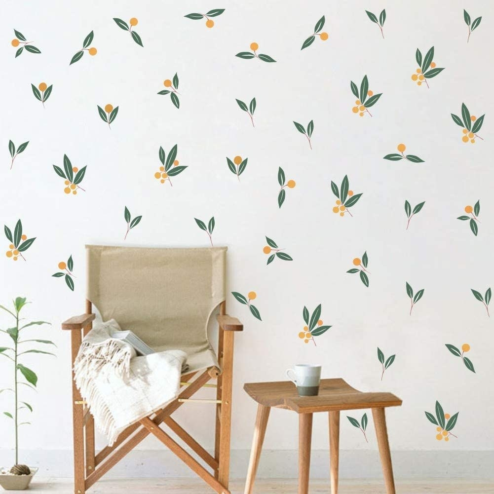 A table and chair in front of a wall covered in tangerine decals