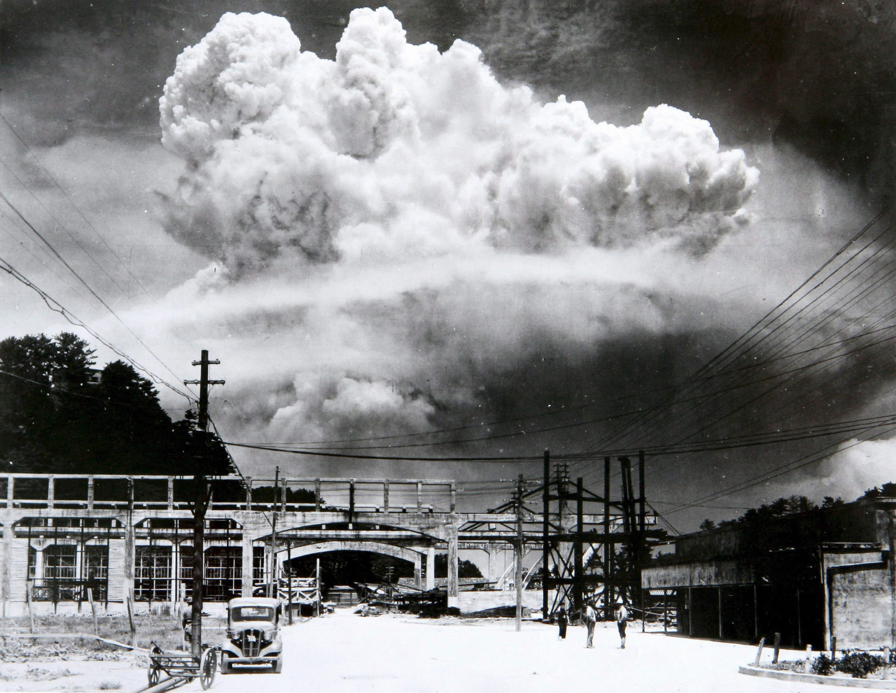 A gigantic atomic mushroom cloud explodes over a bridge and railway station