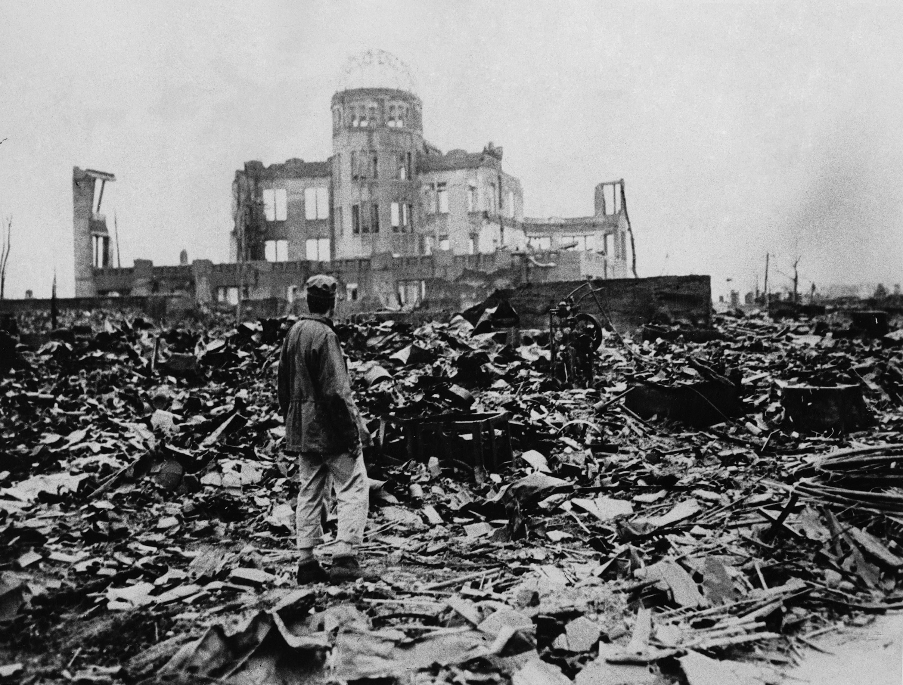 A man walks through rubble looking off to a still-standing building in the distance