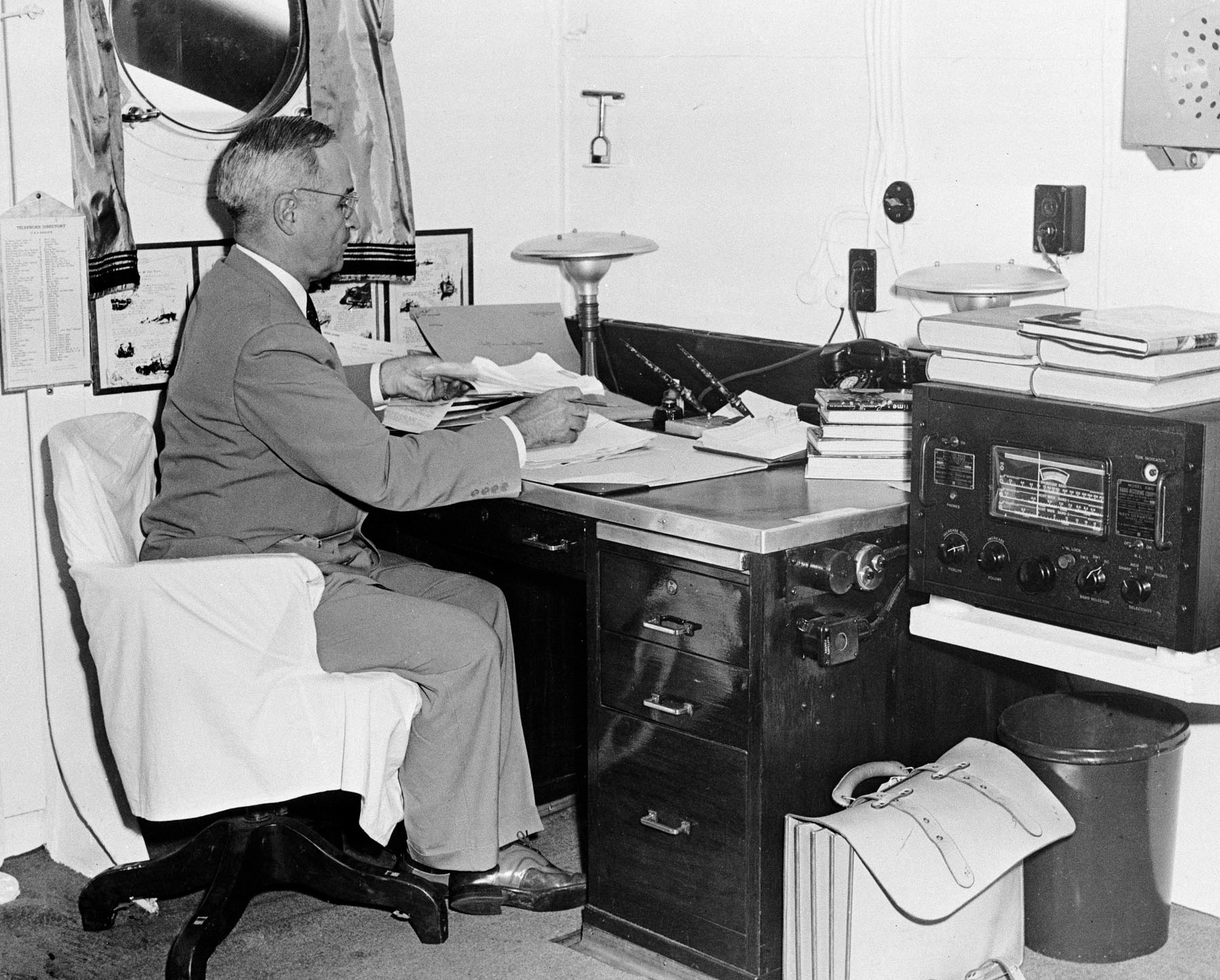 President Harry Truman sits at a desk with papers in front of him and a radio next to him