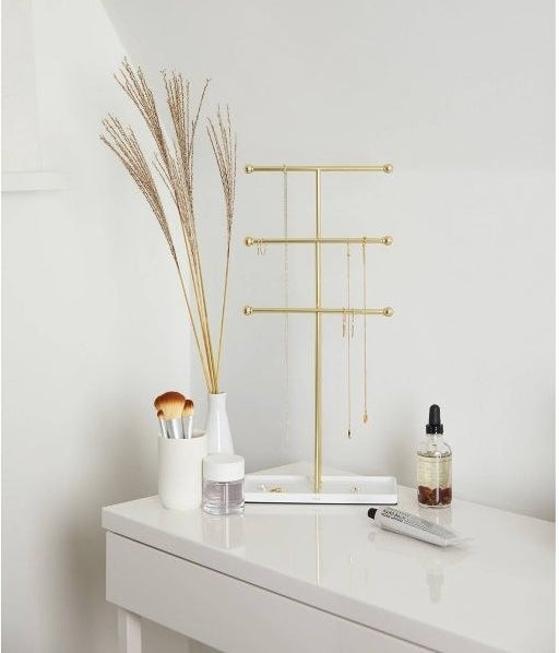 The tall, three-bar organizer with necklaces hanging on the bars and some smaller pieces of jewelry in the white tray base