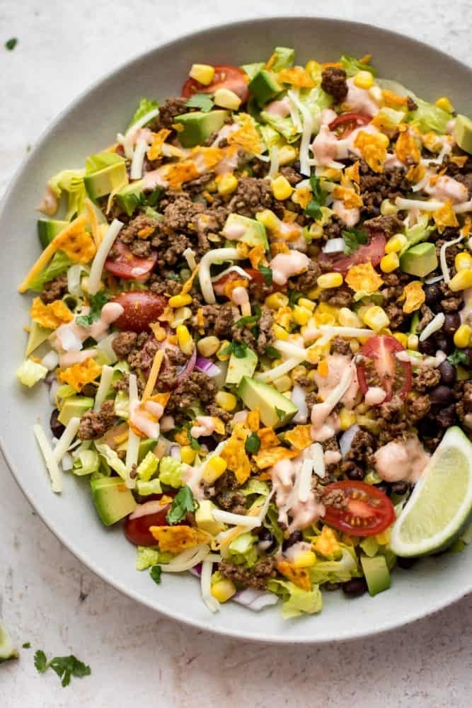 A salad with ground beef, corn, avocado, cabbage, shredded cheese, tomato, and lime.
