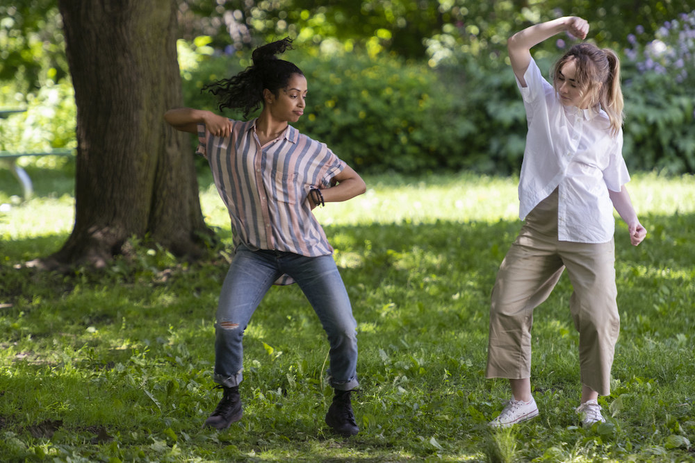 Two girls dance in a park