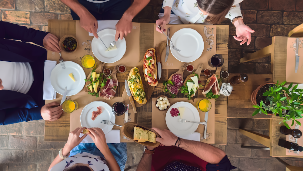A table is set with meats,cheeses and toasts.