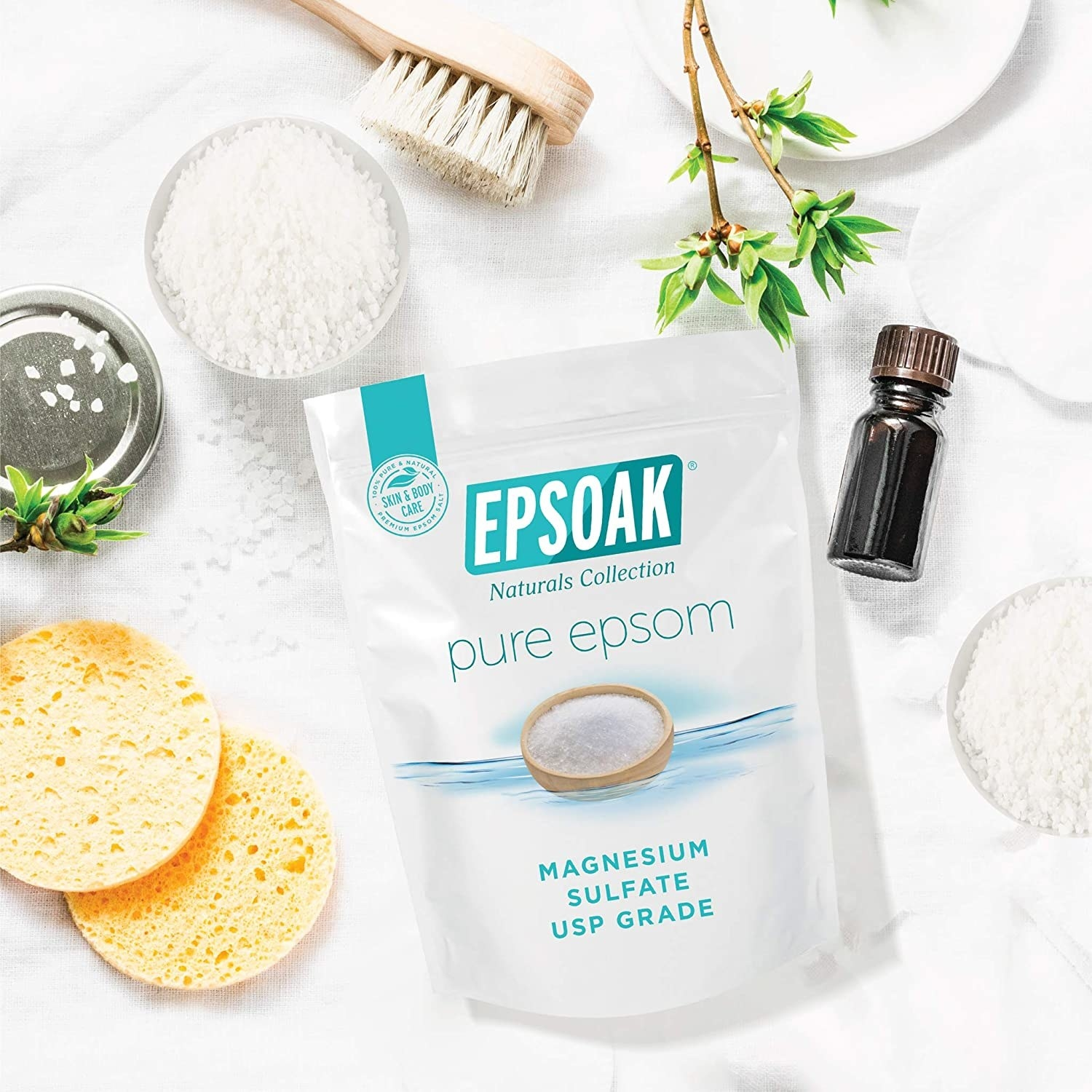 A flatlay of the epsom salts next to sponges and body brushes