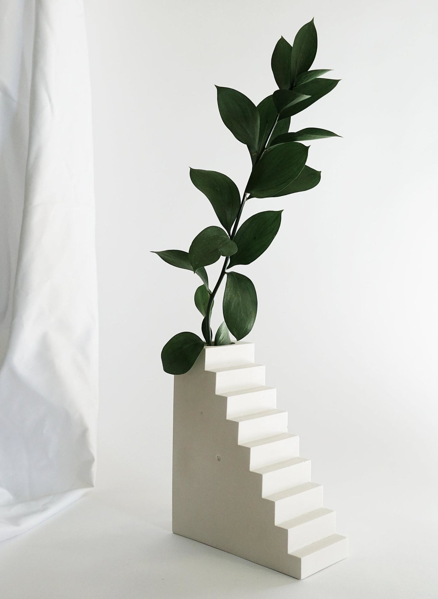 white concrete vase shaped like a flight of stairs with a small rectangular opening on top holding a leafy branch