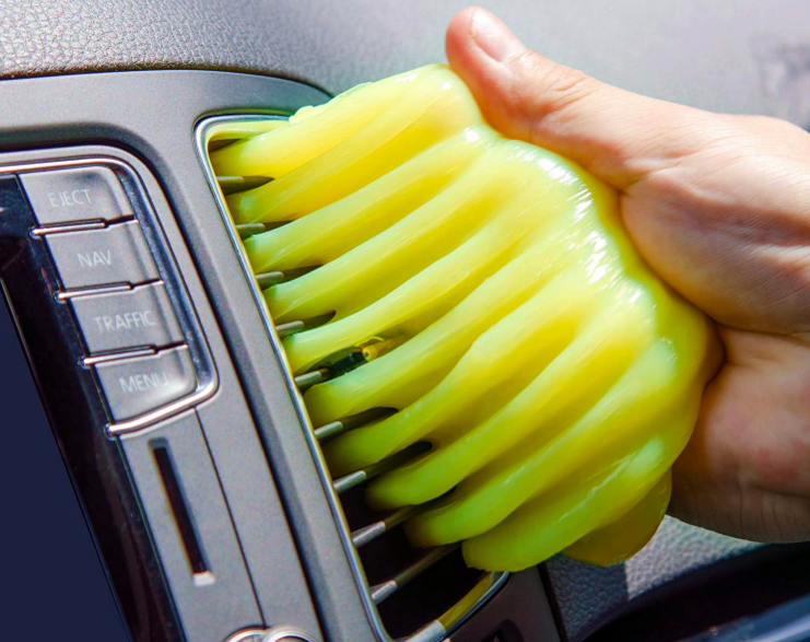 A person using the putty to clean the interior of their car