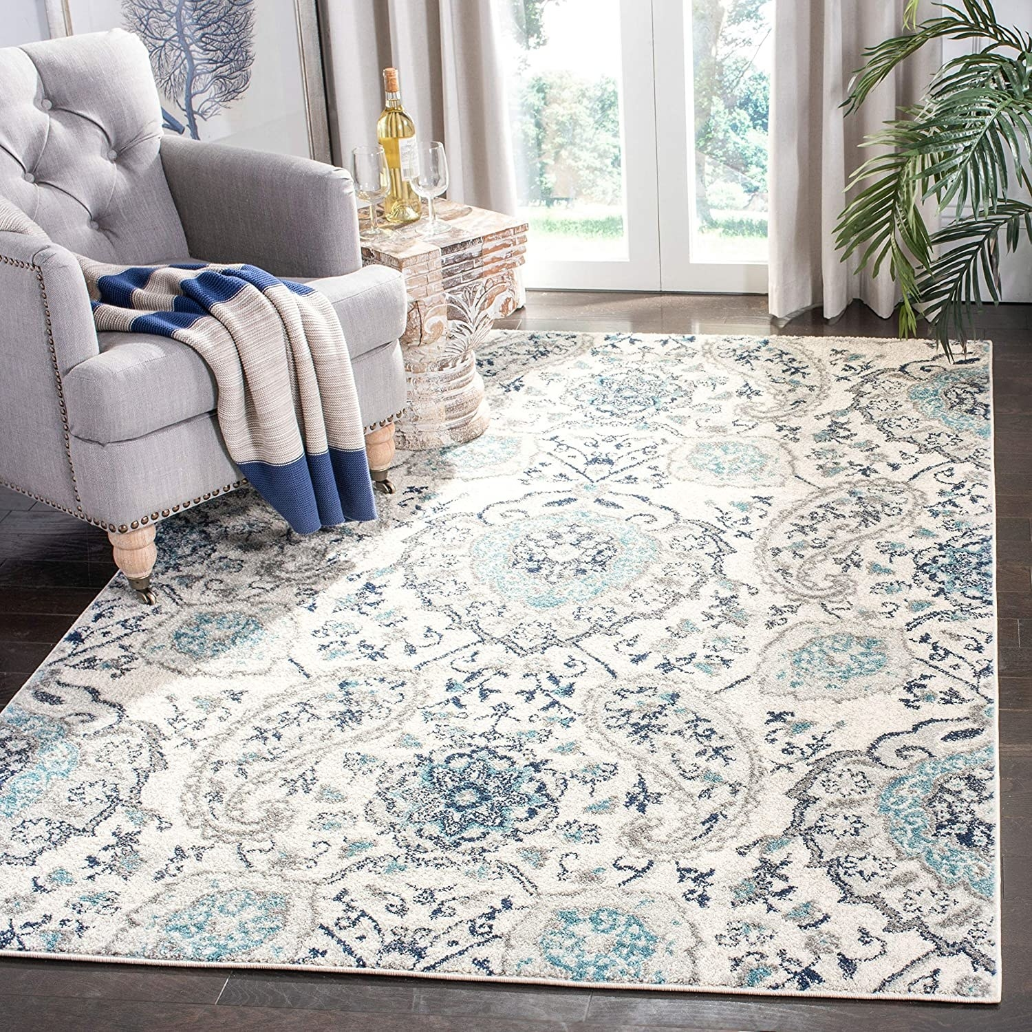 A bohemian, somewhat paisley patterned rug that is blue and white in a living room