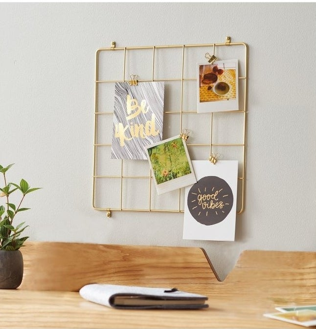 The square organizer on a wall with photos and postcards clipped to it