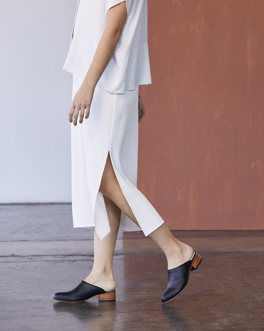 model wearing the mules in black. They completely cover the toes and the top of the foot and they have an exposed ankle and small natural wood heel.