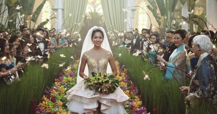 Araminta walking down a floral aisle in an extravagant wedding dress
