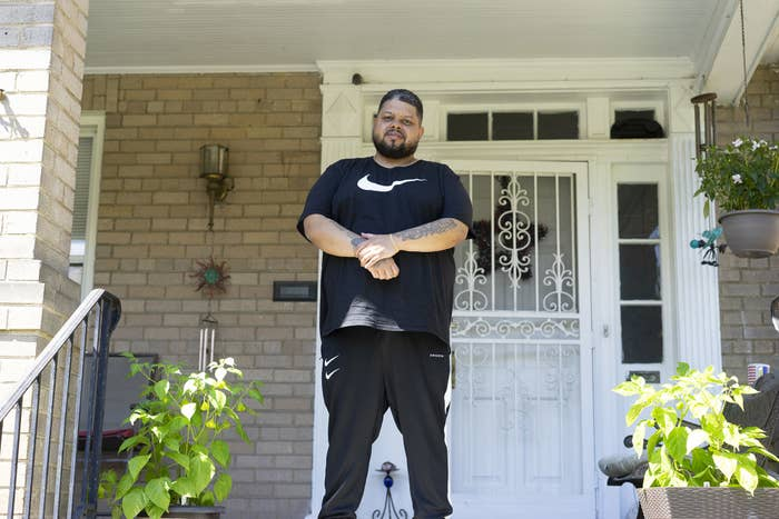 Boykin, who is Black, stands on the front porch of his parent's house wearing a Nike shirt and pants with his arms crossed after being released from prison