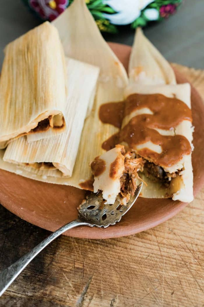 A rustic plate holds an old-fashioned spoon and a pile of tamales topped with a rich mole sauce as shreds of moist chicken peek out beneath the masa.