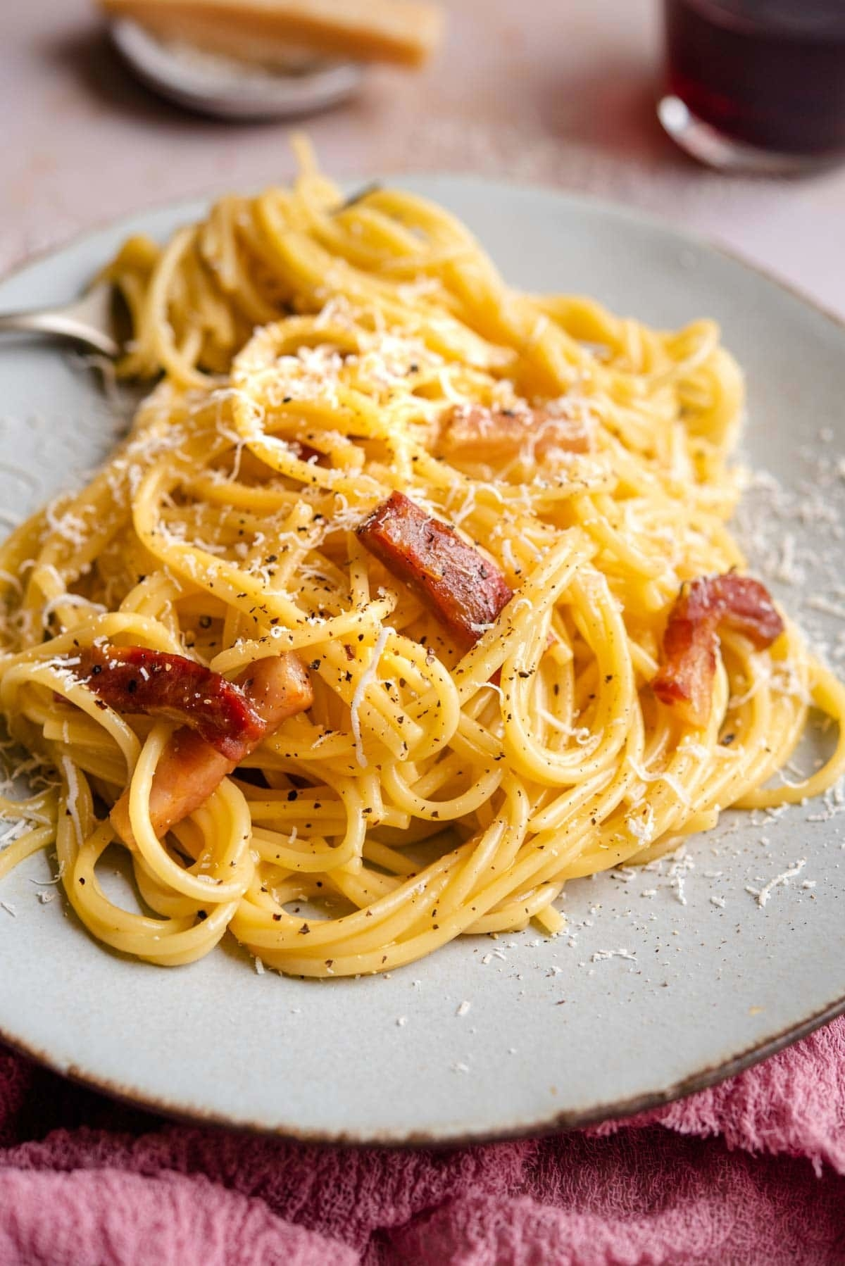 A bed of creamy noodles studded with crispy bits of pork, delicate shreds of cheese, and fresh cracked pepper.