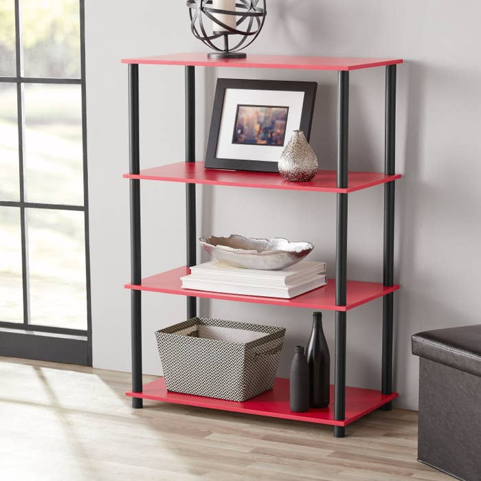 an open bookcase with red shelves