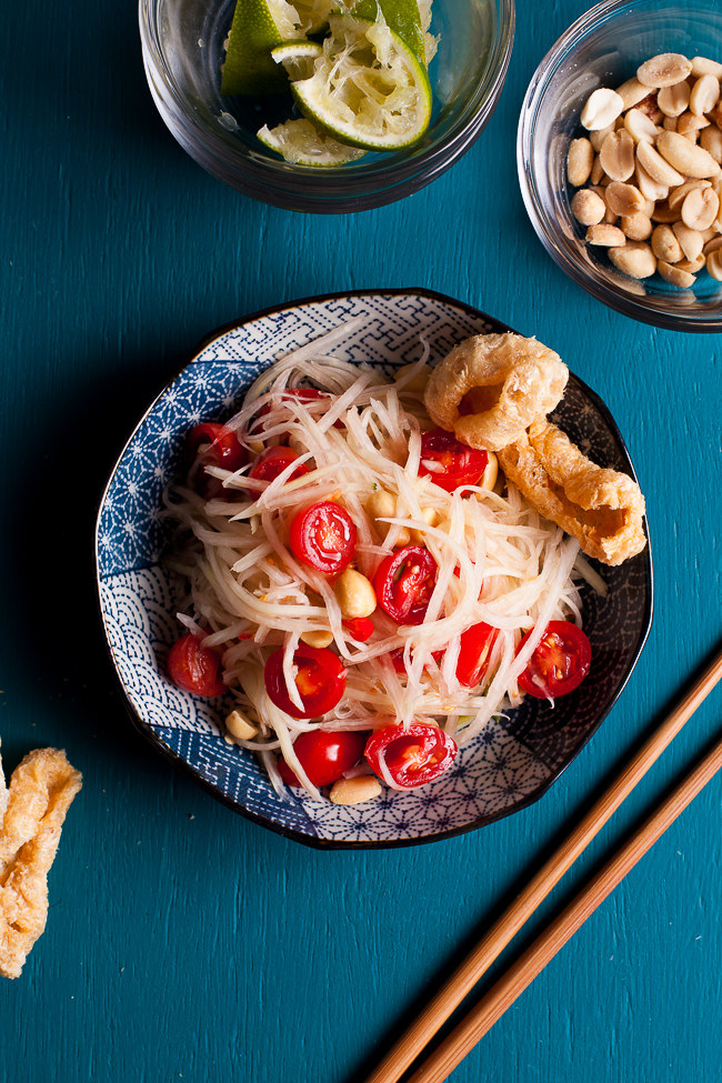 Shreds of green papaya, juicy tomatoes, and peanuts sit in a blue patterned bowl