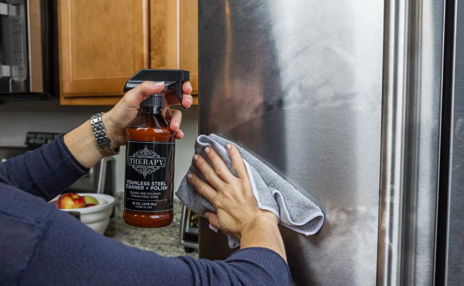 Hand uses bottle of Therapy Stainless Steel Cleaner + Polish and microfiber cloth to wipe away smudges from the front of a fridge