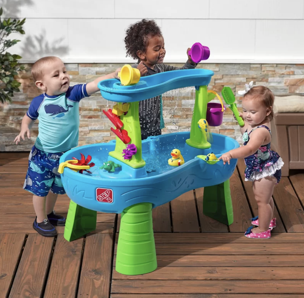 Three kids playing with the water table