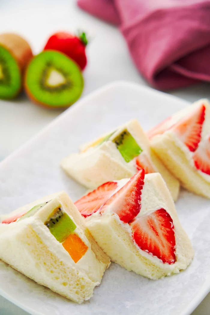 Four sandwiches made of soft white bread, fluffy whipped cream, and fresh slices of fruit