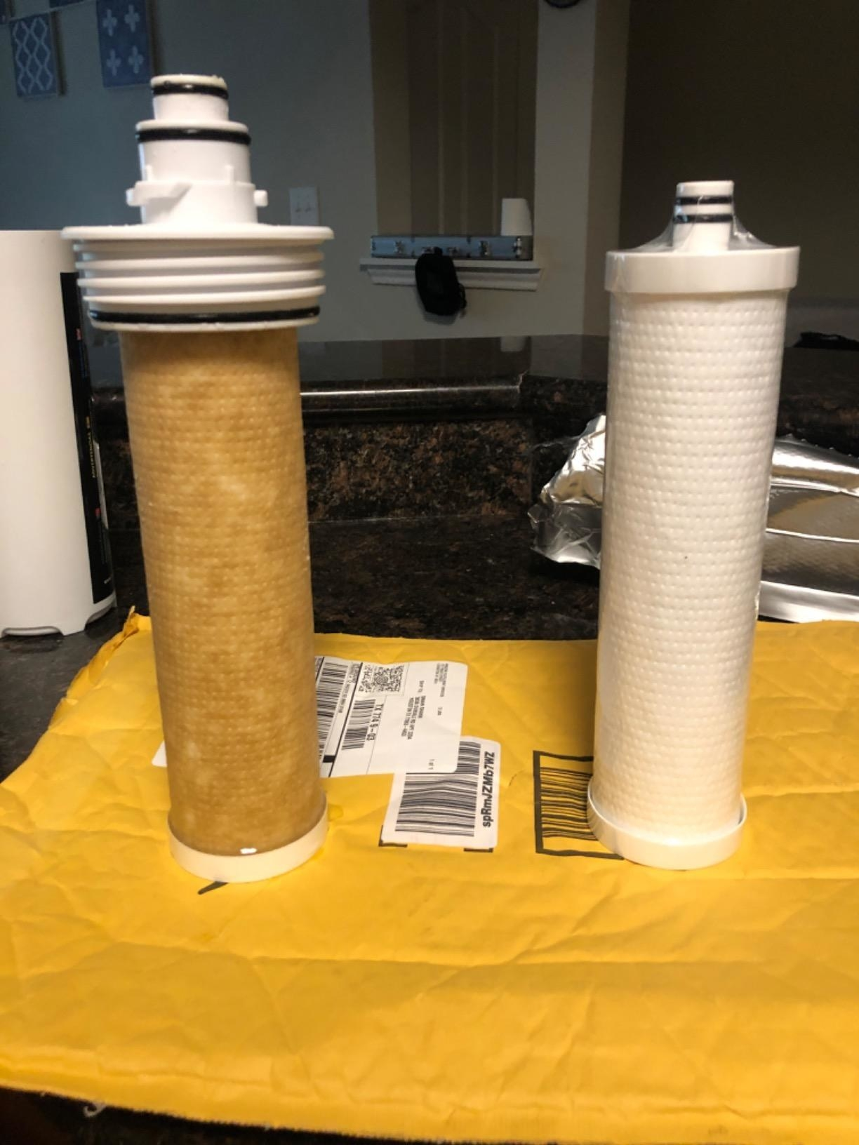 A reviewer photo showing a used filter turned completely brown, and an unused one that's all white