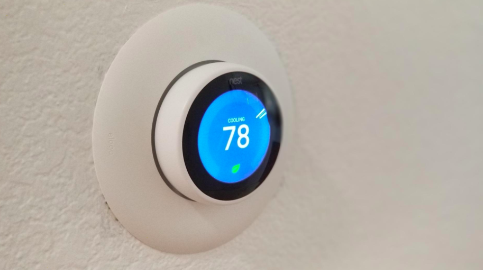 """Reviewer photo of Nest thermostat on wall displaying """"cooling 78"""" on the screen"""