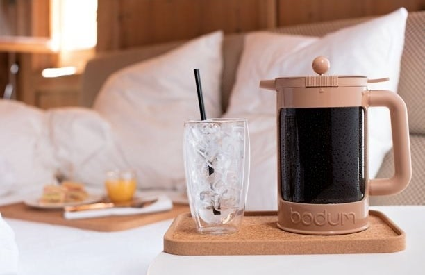 the cold brew maker next to a glass of ice and a cozy breakfast in bed set up