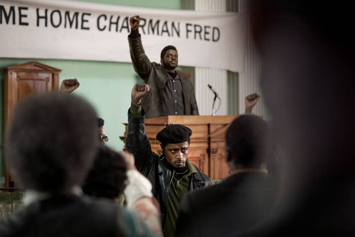 A scene from the movie at a Black Panther meeting with members raising their fists in unity