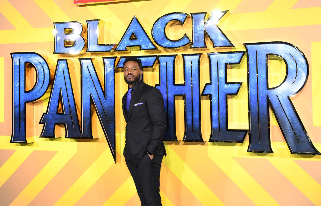 Ryan Coogler standing in front of a Black Panther sign at the film premiere