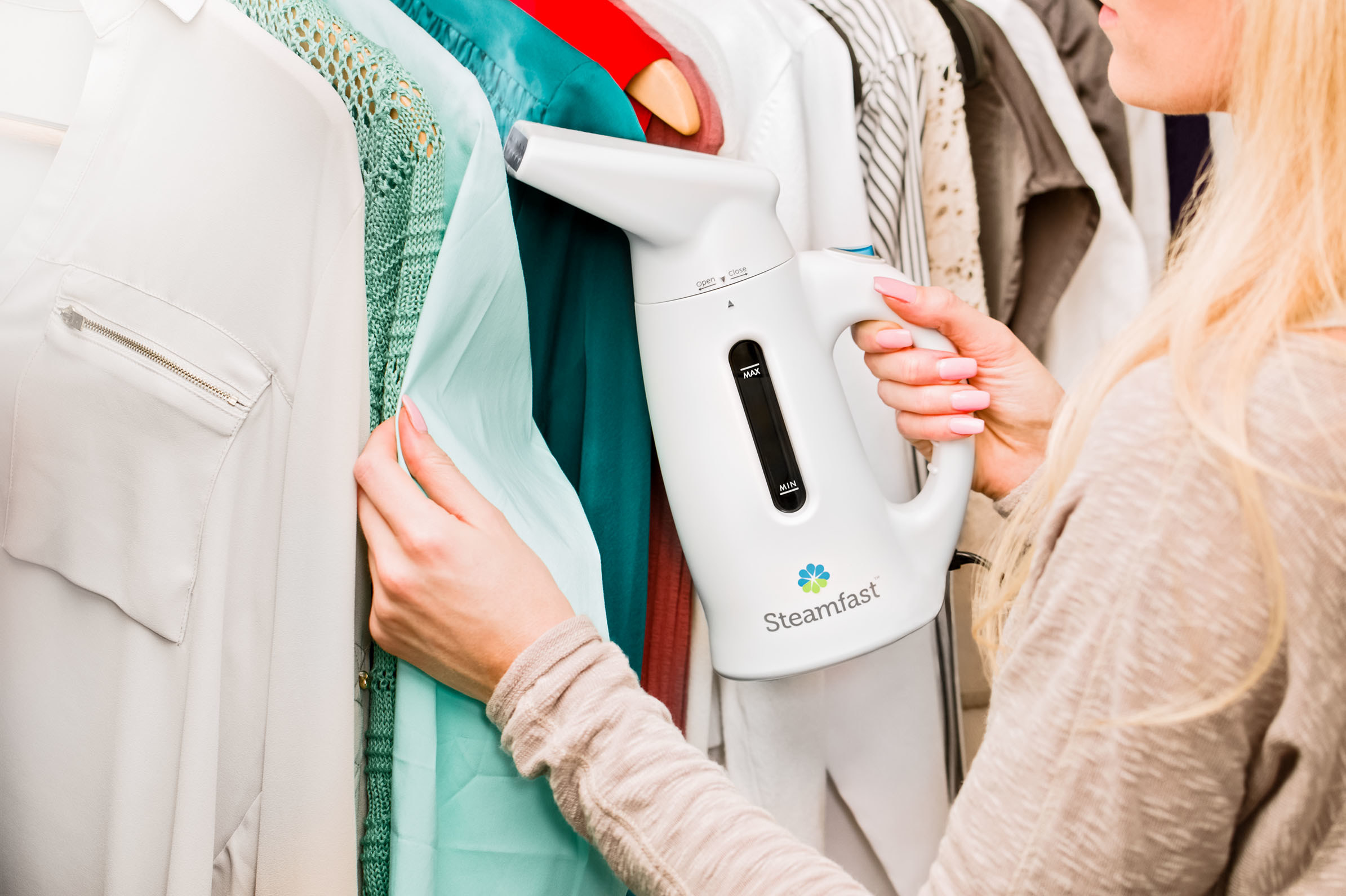a model using the handheld steamer to steam clothes