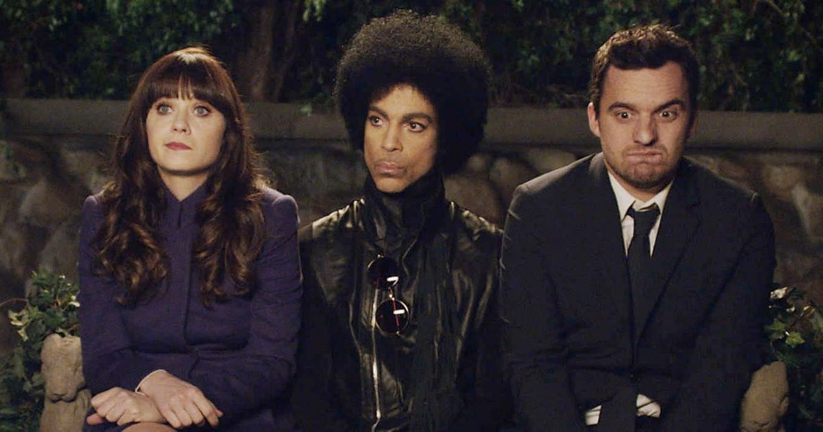 Zooey Deschanel as Jessica and Jake Johnson as Nick Miller sitting next to Prince in New Girl