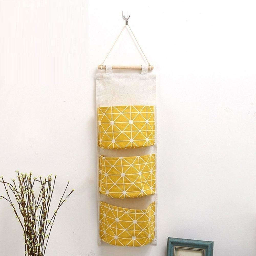 A yellow storage pouch hung up on a wall.