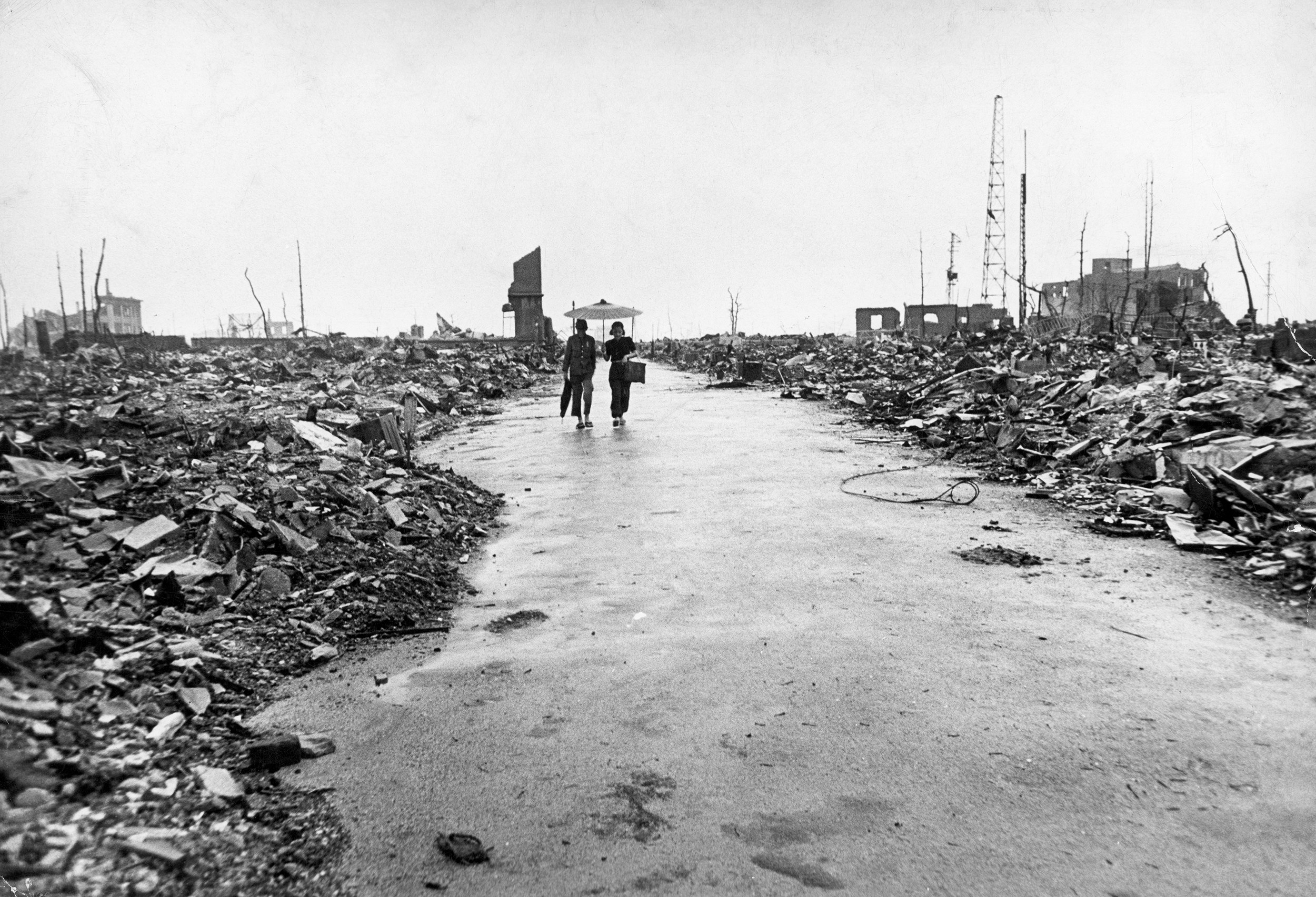 Two people holding an umbrella walk down a destroyed street with rubble on either side