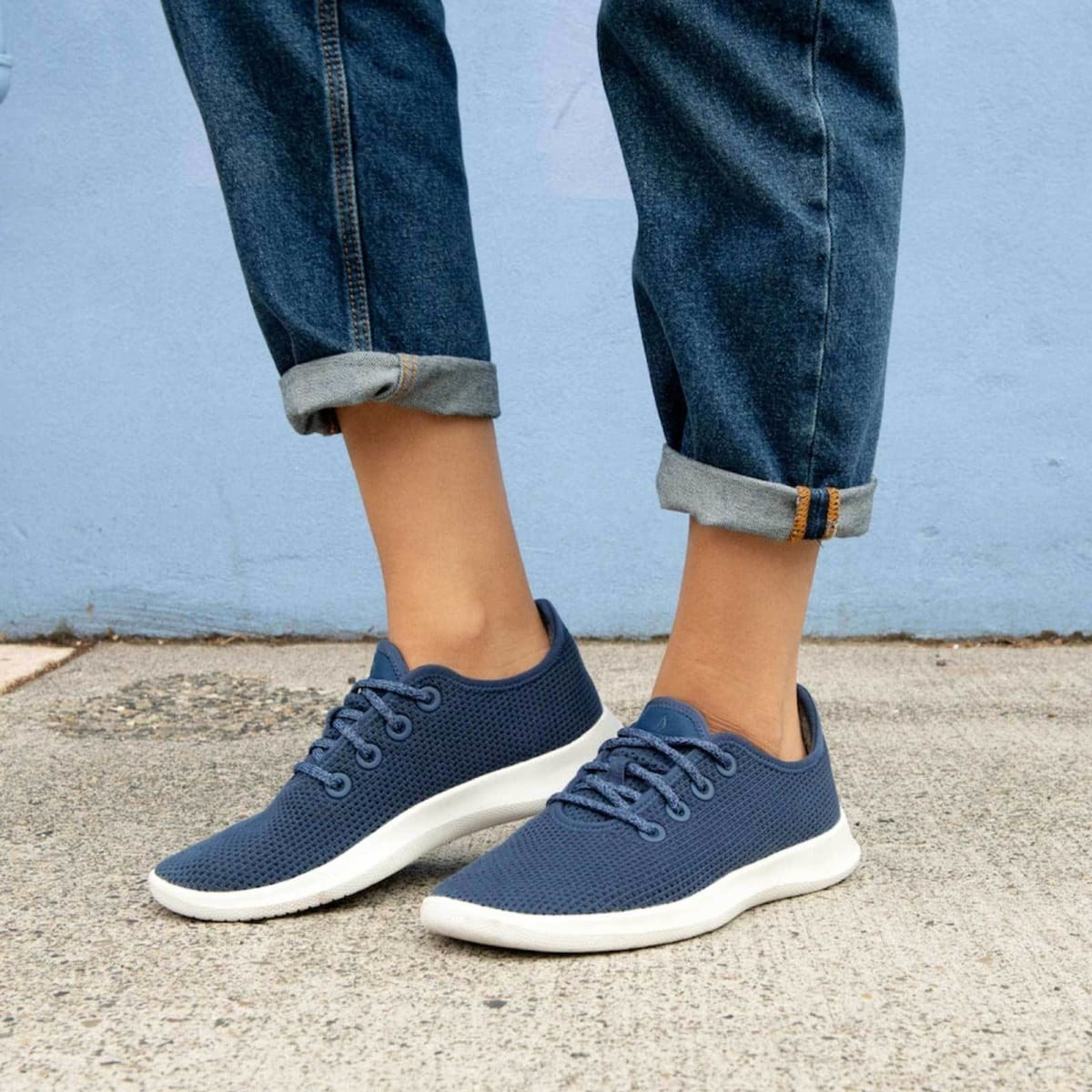 Model wearing the knit sneakers in blue with blue laces and white soles