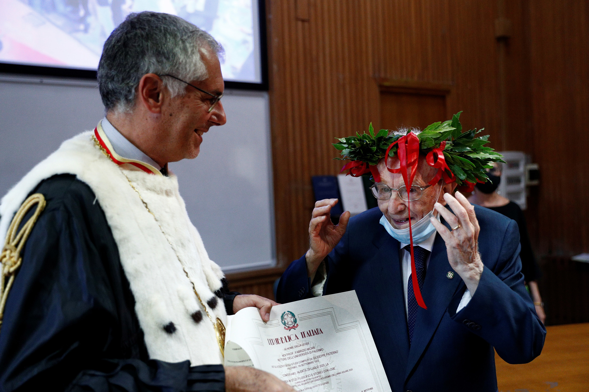 An old man with a suit wearing a crown of laurels smiles while another man, slightly younger and dressed as a college dean hands him a graduation certificate