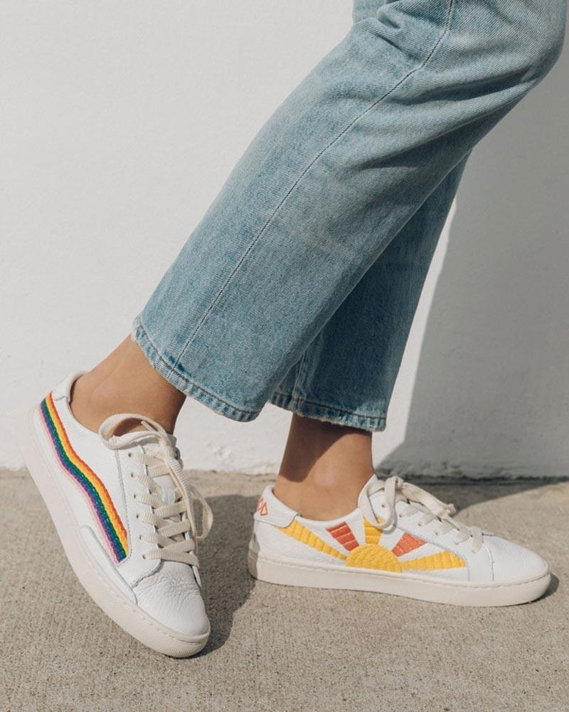 White sneakers with embroidered rainbow along the outsides and embroidered sun in yellow and orange along the insides